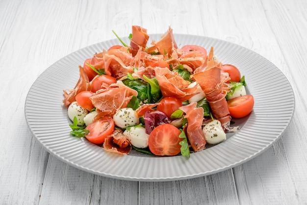Salade met verse groenten met gedroogde tomaten, vlees en mosterd, mozzarella, prosciutto