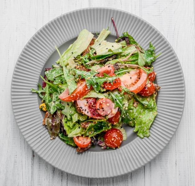 Salade met verse groenten met gedroogde tomaten, vlees en mosterd.