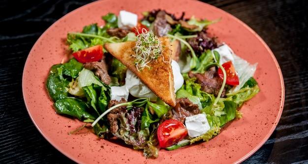 Salade met vlees en groenten op een plaat.
