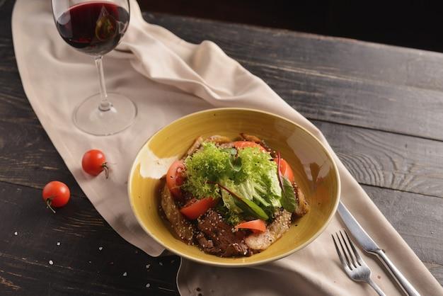 Salade met vlees, tomaten, sesamzaadjes en sla. in een gele plaat op een houten tafel