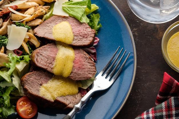 Salade met warm rundvlees met oesterzwammen, tomaten en groenten. bovenaanzicht