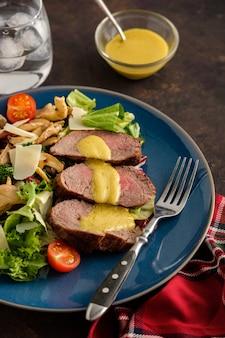 Salade met warm rundvlees met oesterzwammen, tomaten en groenten.