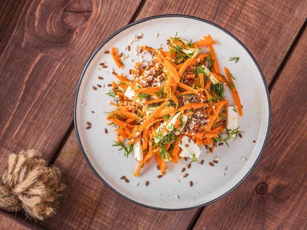 Salade met wortelen en kaas en granen zaden op een vintage dienblad bovenaanzicht