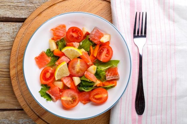 Salade met zalm en kerstomaatjes en groene salade in een plaat op een houten tafel op een houten standaard met een vork en servet ernaast