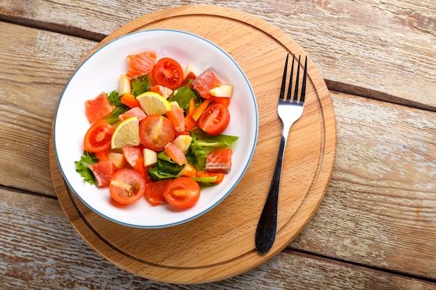 Salade met zalm en kerstomaatjes en groene salade in een plaat op een houten tafel op een houten standaard staan naast een vork