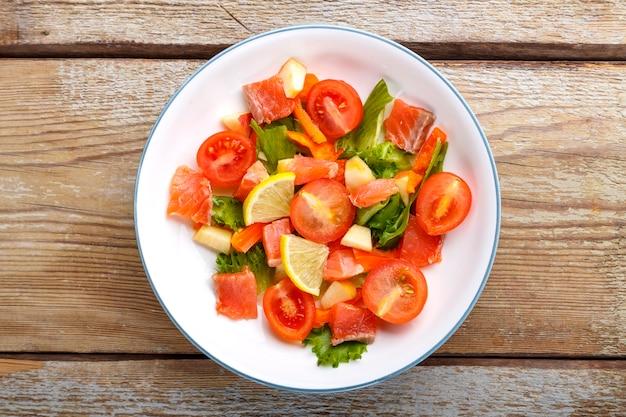 Salade met zalm en kerstomaatjes en groene salade in een plaat op een houten tafel