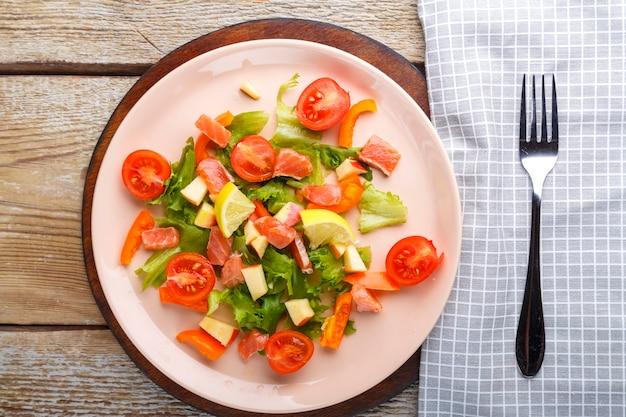 Salade met zalm en kerstomaatjes in een plaat op een houten tafel op een houten standaard staan naast een vork en een servet