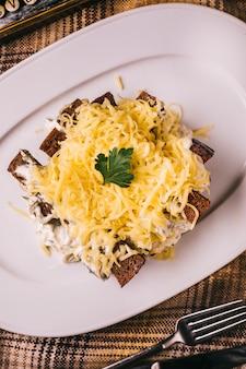 Salade met zwart brood en gehakte kaas.