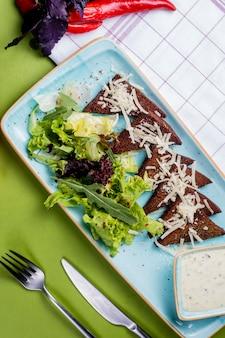 Salade met zwart zijbrood gegarneerd met kaas