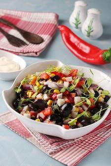 Salade met zwarte bonen, maïs, krabsticks en erwten microgrines in een witte kom