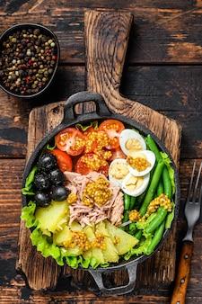 Salade nicoise met tonijn, cherrytomaatjes, olijven, sperziebonen, komkommer, zachtgekookte eieren en aardappel.
