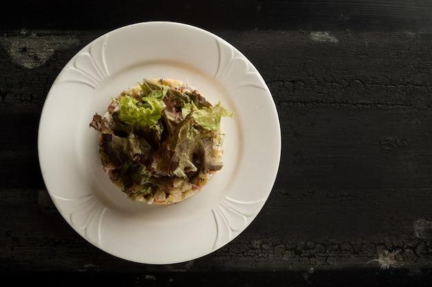 Salade olivier in een wit bord op een houten oud oppervlak olivier salade met groen in een rond bord
