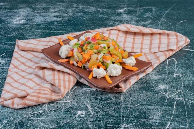 Salade op een houten schotel met gehakte ingrediënten en kruiden.