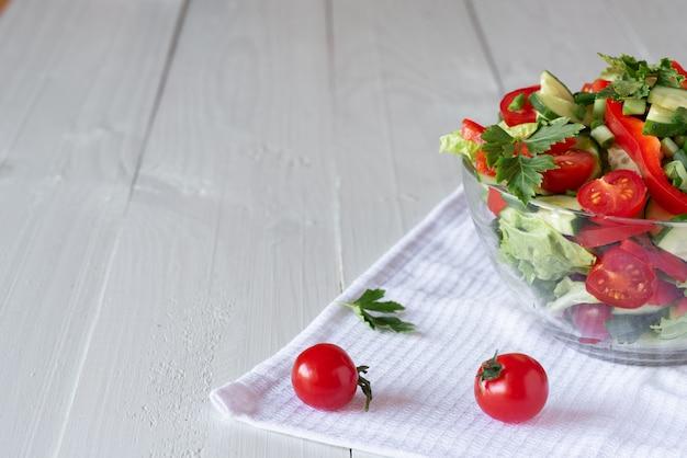 Salade op een witte houten achtergrond van tomaten, komkommer, sla en rode peper. gezond eten concept.