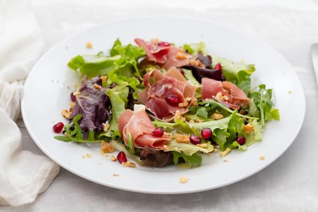 Salade prosciutto met granaatappel op een witte plaat