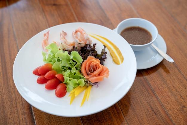 Salade rauwe zalm gerangschikt naar roze vorm en gekookte garnalen naast in de witte schotel op houten tafel.