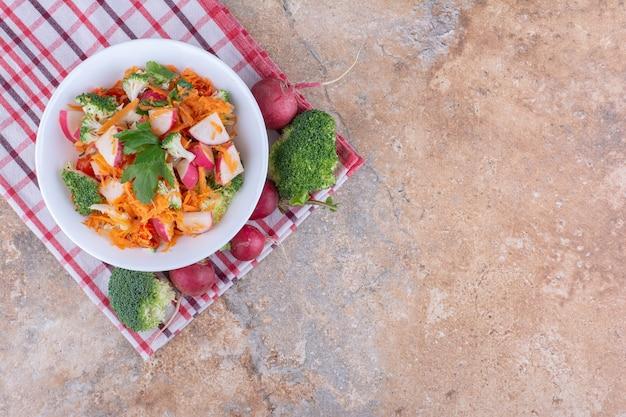 Salade schotel volgende van verschillende groenten op een handdoek op marmeren oppervlak
