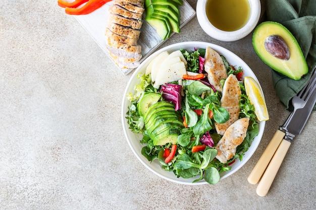 Salade van avocado, appel, paprika en gegrilde kip met ingrediënten voor het maken van salade.