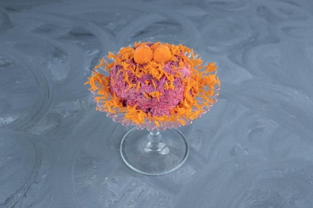 Salade van bieten en walnoten gegarneerd met wortel en geserveerd op een glazen voetstuk op een marmeren oppervlak.