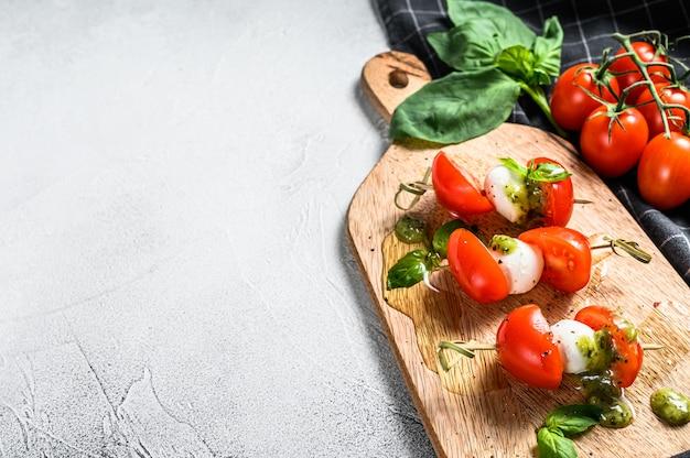 Salade van caprese aan het spit, tomaat, pesto en mozzarella. canapeetjes snack. grijze achtergrond. bovenaanzicht. kopieer ruimte