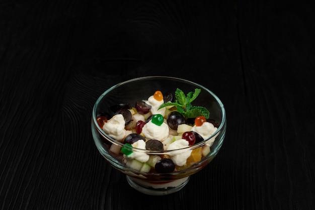 Salade van druiven appels peren kiwi sinaasappels met mascarpone kaas en room. gezonde verse fruit zomersalade in glazen kom op zwarte houten achtergrond met kopie ruimte.