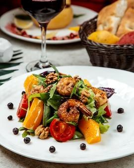 Salade van gebakken garnalen met sla, rucola, sinaasappel, tomaten, walnoot en donkere opaal basilicum