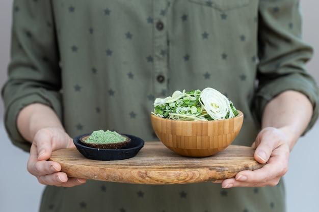 Salade van gedroogde groenten naast groen poeder dat wordt gebruikt voor veganistisch eten