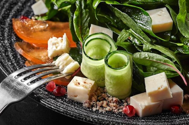 Salade van geitenkaas en kaki met groen komkommers granaatappel walnoten