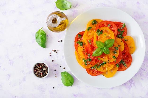 Salade van gele en rode tomaat met basilicumpesto op een lichte lijst. plat liggen. bovenaanzicht
