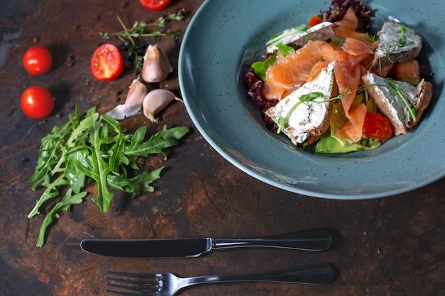 Salade van gerookte zalm met groenten, tomaten, eieren en avocado