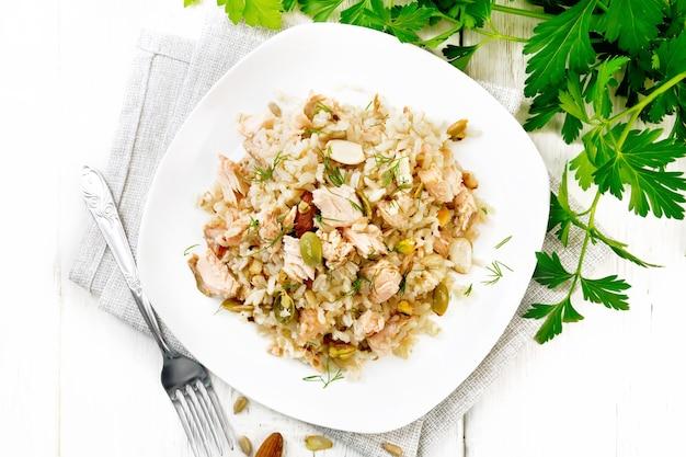 Salade van gerookte zalm, rijst, zonnebloem- en pompoenpitten, amandelen, gekruid met honing en olijfolie in een bord op een handdoek, peterselie en vork op een houten plankachtergrond van bovenaf