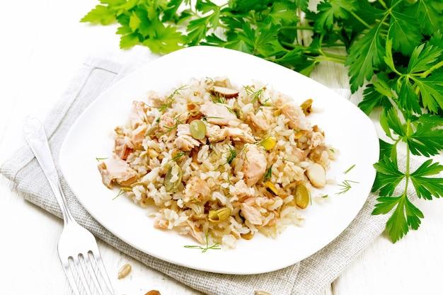 Salade van gerookte zalm, rijst, zonnebloem- en pompoenpitten, amandelen, gekruid met honing en olijfolie in een bord op een handdoek, peterselie en vork op houten plankachtergrond