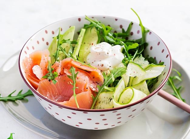 Salade van gezouten zalm, avocado en komkommer met roomkaas in witte kom