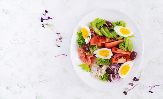 Salade van gezouten zalm en gebakken dorado met groenten, tomaten, eieren en avocado