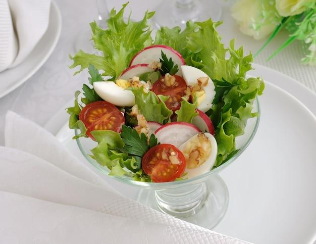 Salade van kerstomaatjes met kwartelei en radijs in de slablaadjes
