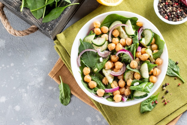 Salade van kikkererwten, spinazie, komkommers, uien en groenten in een bord