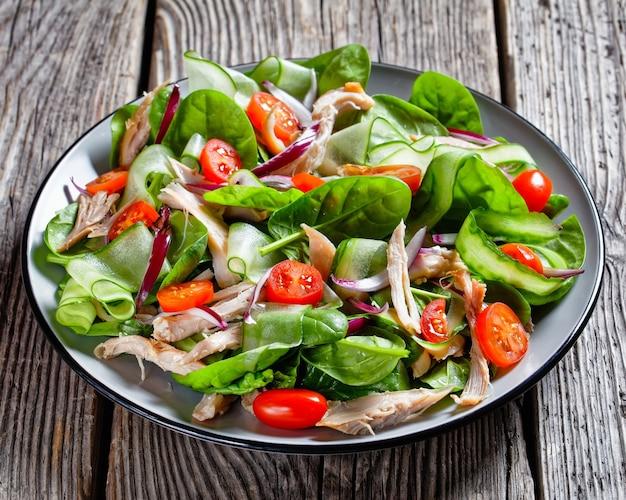 Salade van kipfilet en verse babyspinazieblaadjes, kerstomaatjes, komkommerlint, rode uienringen met olijfolie en citroendressing, geserveerd op een bord op een houten tafel, bovenaanzicht, close-up
