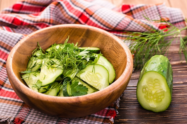 Salade van komkommers met kruiden in een houten plaat