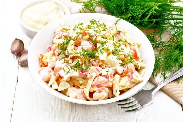 Salade van krabsticks, kaas, knoflook, eieren en tomaten, gekleed met mayonaise in een bord, servet en peterselie op een houten plankachtergrond