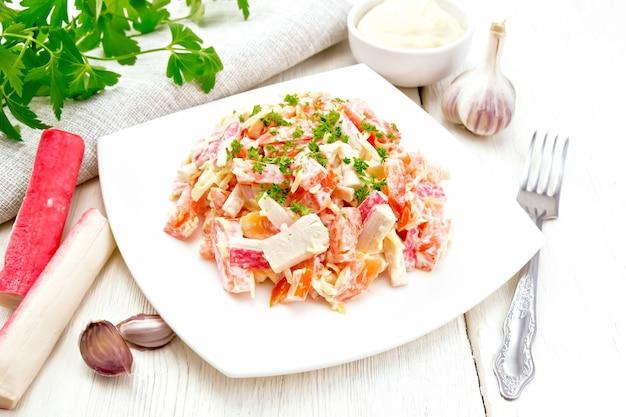 Salade van krabsticks, kaas, knoflook en tomaten, gekleed met mayonaise, servet en peterselie op een houten plankachtergrond
