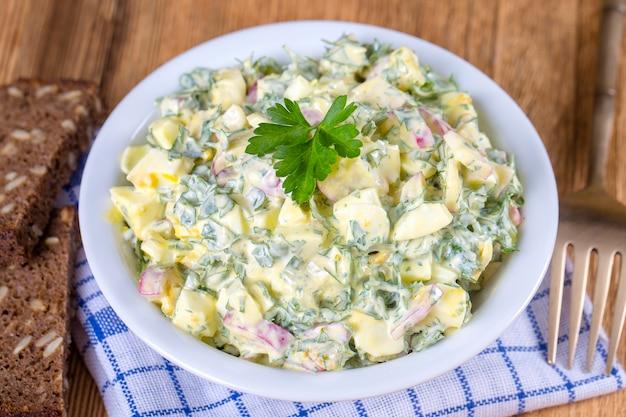 Salade van radijs, gekookt ei, peterselie en zure room in witte kom