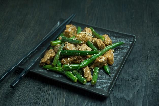 Salade van sperziebonen en vlees, bestrooid met sesamzaadjes. het dienen van hete salade met slabonen. aziatisch eten. donkere houten achtergrond.