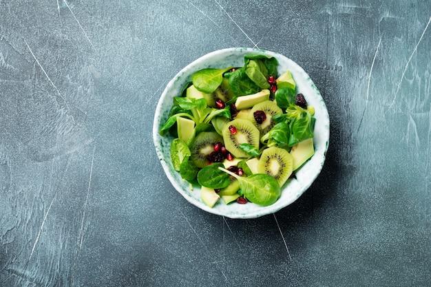Salade van spinazie babyblaadjes, waterkers, kiwi, avocado en granaatappel in een oude keramische plaat op een grijze betonnen achtergrond
