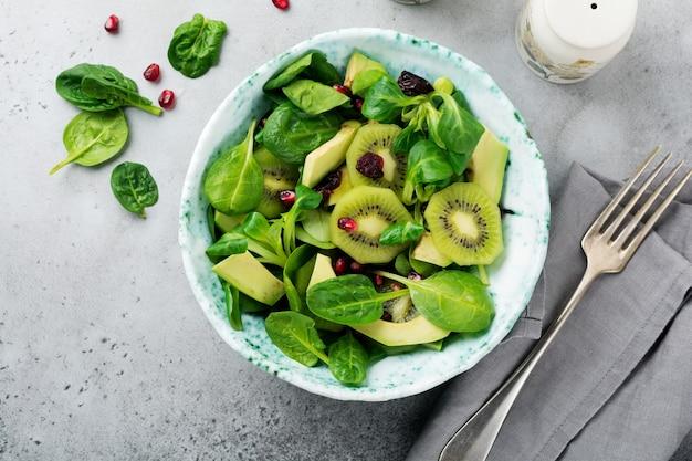 Salade van spinazie babyblaadjes, waterkers, kiwi, avocado en granaatappel in een oude keramische plaat op een grijze betonnen ondergrond. selectieve aandacht. bovenaanzicht.