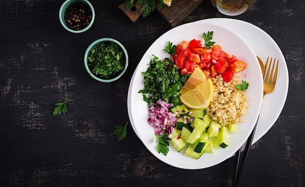 Salade van tabouleh. traditioneel midden-oosters of arabisch gerecht. levantijnse vegetarische salade met peterselie, munt, bulgur, tomaat. bovenaanzicht