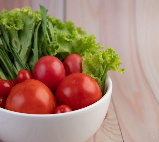 Salade van tomaten en lente-uitjes in een witte kop op een houten vloer.