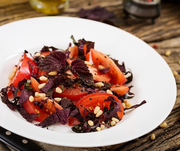 Salade van tomaten met een violet basilicum en pijnboompitten. veganistisch eten. italiaanse maaltijd.