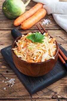 Salade van vers geraspte wortelen en groene radijs met saus.
