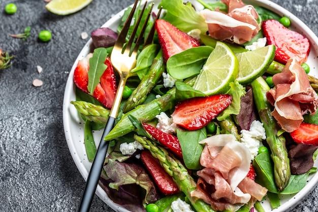 Salade van verse groene asperges, aardbei, rucola en kwark