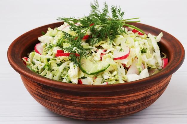 Salade van verse groenten: kool, radijs, komkommer, ui en dille, in een bruine slakom